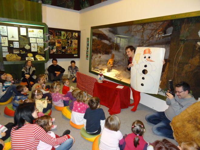 Manó Múzeum Béres Erikával Kaposváron. A nagy vitrin előtt bábozik, a gyerekek feszülten figyelnek.